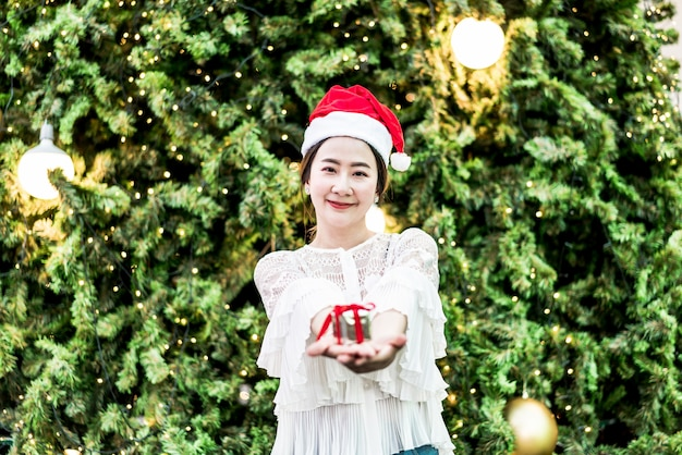 お祝いクリスマスフェアのギフトを持つ笑顔の美しい若いアジア女性の肖像画