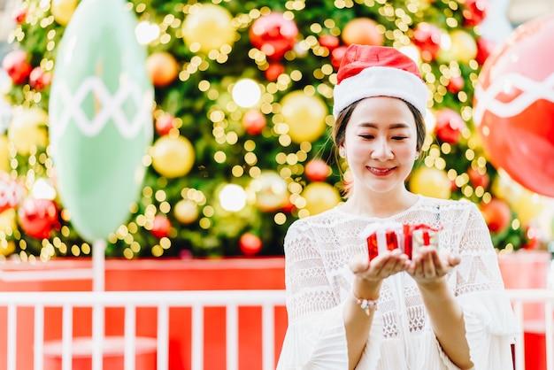 Портрет улыбающегося красивой молодой азиатской женщины с подарком на праздничной рождественской ярмарке