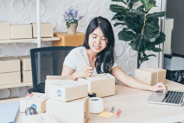 中小企業のオーナー、ノートパソコンで注文をチェックする女性