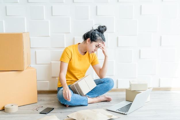 若いアジアの女性は彼女のラップトップの前にストレスを感じるか、落ち込む