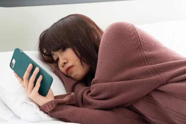 ベッドの上でスマートフォンを遊んでいるアジアの女性