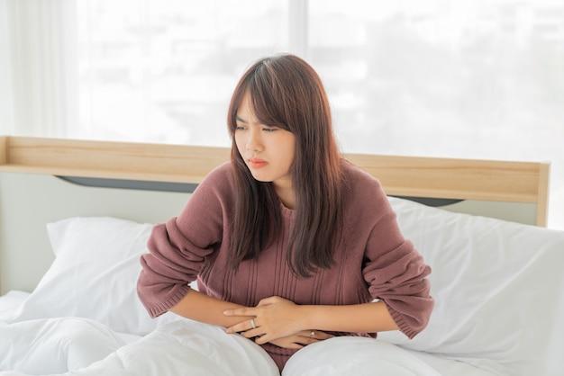 アジアの女性の腹痛とベッドで寝ています。