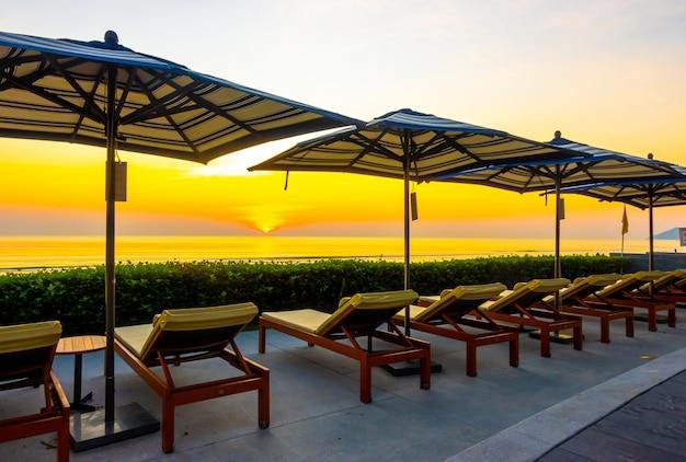 傘と休日休暇旅行背景のホテルリゾートの屋外スイミングプールの周りの椅子