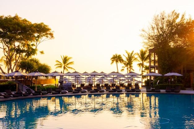 Зонтик и лежак возле открытого бассейна в отеле-курорте для путешествий и отдыха