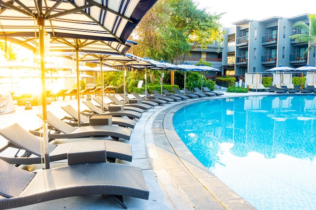 旅行休暇休暇のためのホテルリゾートの屋外スイミングプールの周りの傘とプールベッド