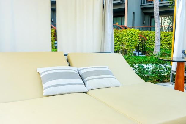 旅行休暇休暇のためのホテルリゾートの屋外スイミングプールの周りの傘と椅子のソファ