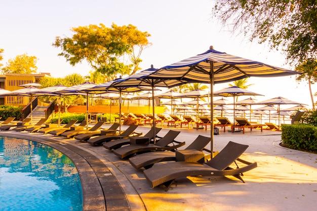 Красивый тропический пляж и море с зонтиком и креслом вокруг бассейна в отеле-курорте для путешествий и отдыха