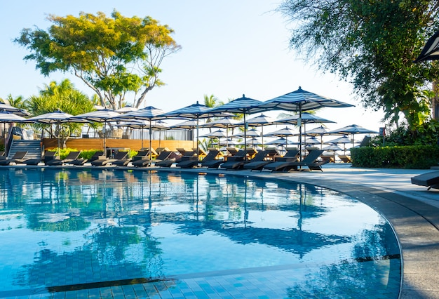 美しい豪華な傘とホテルと青い空とリゾートの屋外スイミングプールの周りの椅子