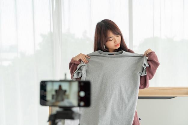 Красивый азиатский блоггер женщины показывая одежды на камере для того чтобы записать видео в реальном маштабе времени видео в ее магазине