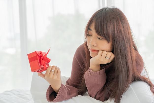 ギフト用の箱を受け取って幸せなアジアの女性
