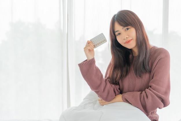 Азиатские женщины держат противозачаточные таблетки