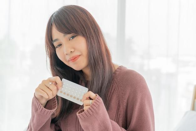 避妊薬を保持しているアジアの女性