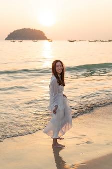 夏の熱帯の砂浜に旅行に行く幸せな女