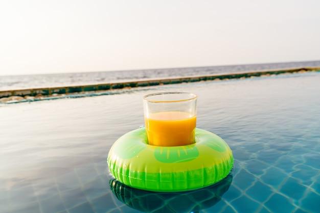 屋外スイミングプールでの水泳リングとオレンジジュースのグラス
