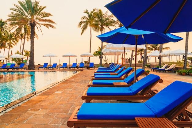 日の出時に高級ホテルリゾートの傘椅子プールとヤシの木