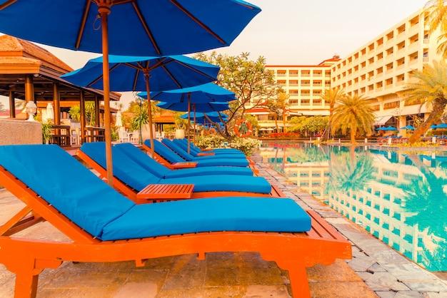 ホテルとリゾートのスイミングプールの周りの美しい傘と椅子
