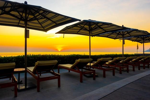 ホテルやリゾートの屋外スイミングプールの周りの傘と椅子