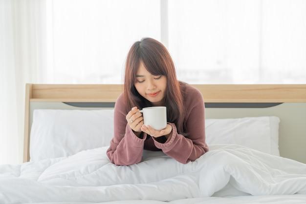 朝のベッドでコーヒーを飲むアジアの女性