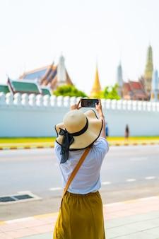 Счастливая азиатская женщина фотографируя висок