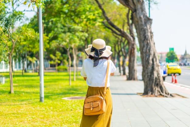 Счастливая азиатская женщина идя по улице