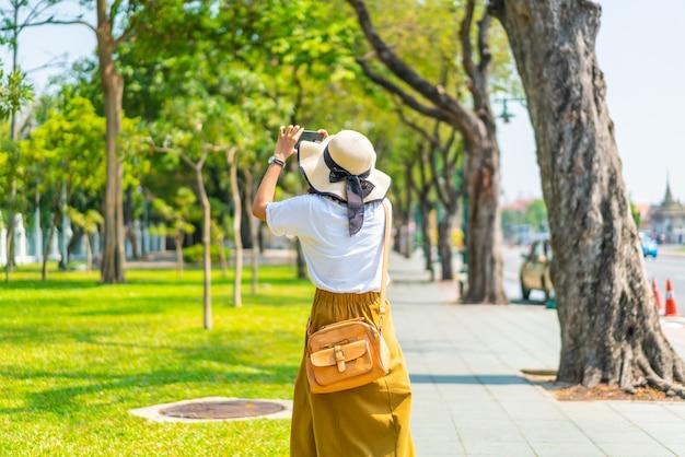 Счастливая азиатская женщина идя по улице и фотографируя
