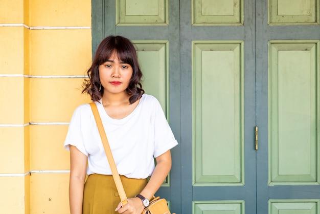 Счастливая азиатская женщина представляя с сумочкой