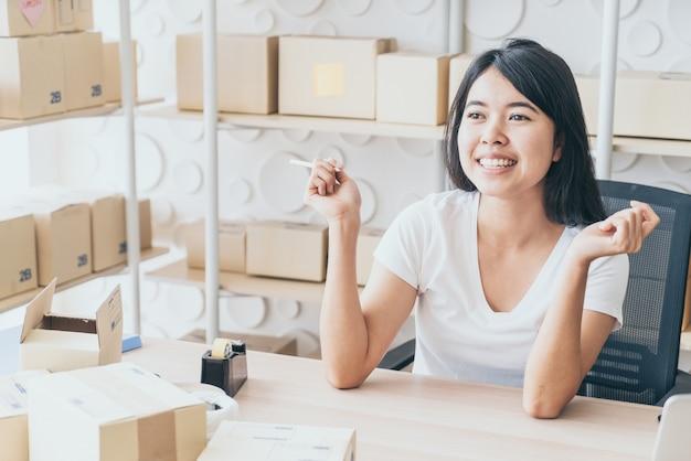 若い女性が顧客、自宅の事業主からの新規注文後に満足