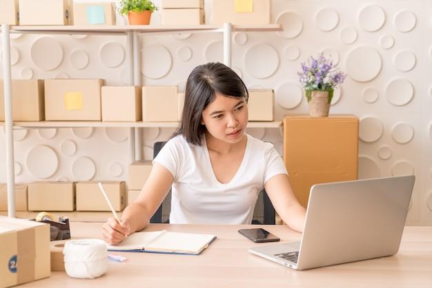 Молодая азиатская женщина, работающая с цифровым планшетом на рабочем месте