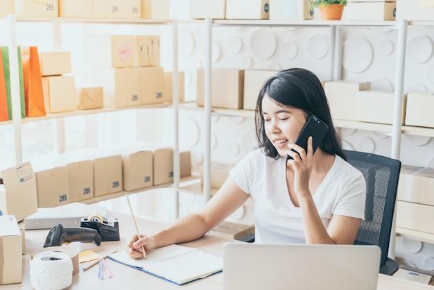 Молодая азиатская женщина запускает владелец малого бизнеса, работающий с цифровым планшетом на рабочем месте