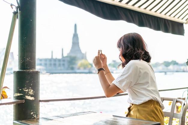カフェで写真を撮るアジアの女性旅行者