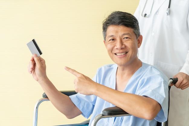 Азиатская старшая терпеливая кресло-коляска усмехаясь с кредитной карточкой