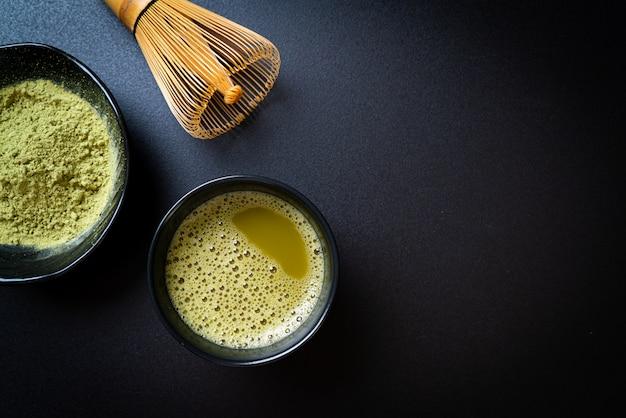 抹茶パウダーと泡だて器のホット抹茶グリーンティーカップ
