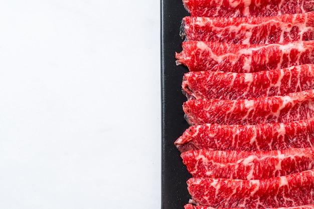 霜降りのテクスチャーでスライスした生の新鮮な牛肉