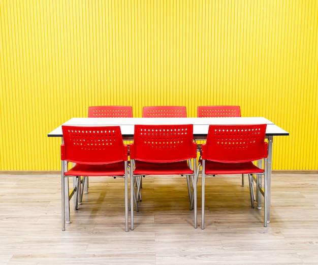Пустой стол и красный стул в комнате