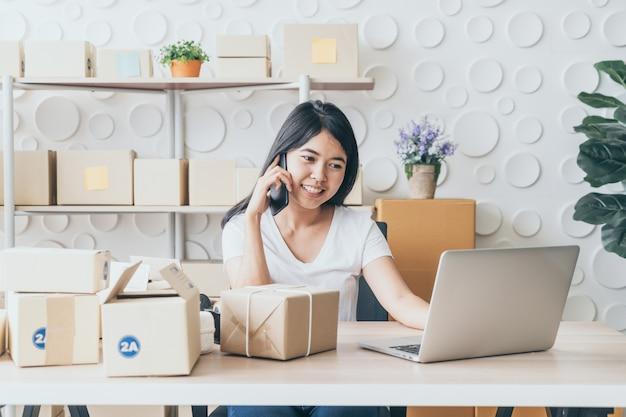 Азиатская женщина наслаждается, используя интернет на ноутбуке и телефон в офисе