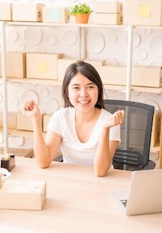 顧客、ビジネスオーナーの自宅からの新規注文後の幸せな若い女性