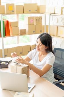 職場で梱包箱を自宅で働くアジア女性ビジネスオーナー