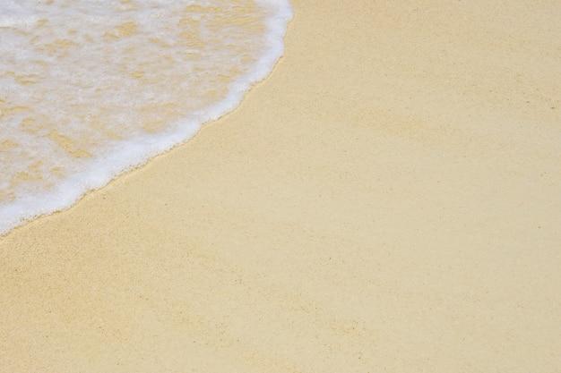 きれいな砂浜のテクスチャ背景に海の美しい柔らかい波