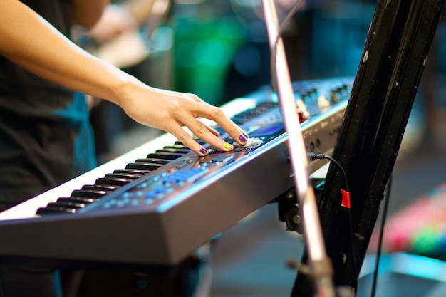 浅い被写し界深度とコンサートでキーボードを演奏するミュージシャンの手は、右手に焦点を当てる
