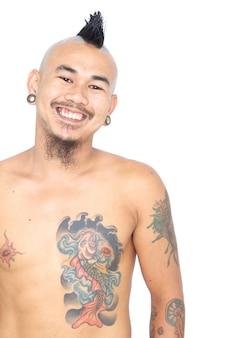 Портрет улыбающегося азиатского парня панка с изолированной прической, пирсингом и татуировкой ирокезом