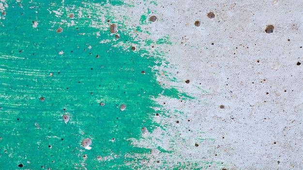 Незавершенная зеленая краска на ровной бетонной поверхности стены