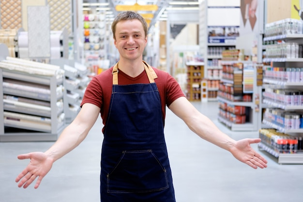 セールスマンは、建設スーパーストアで笑顔で顧客を歓迎します。