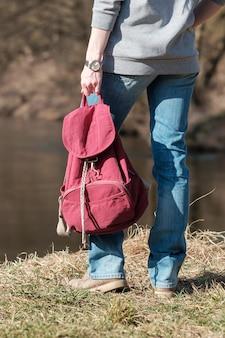 Концепция путешествия. женщина, стоящая на берегу реки, одета в джинсы и серую толстовку, держит красный рюкзак и смотрит вдаль. весенний сезон.