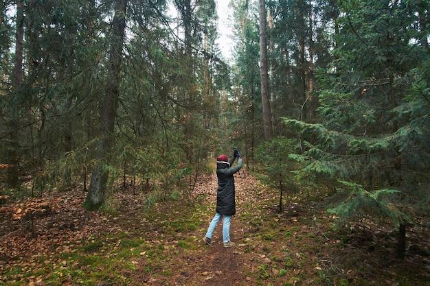 Женщина гуляет в осеннем лесу и делает фотографии на смартфоне