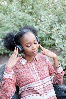 目を閉じてヘッドフォンで音楽を聴く民族衣装で黒のアフロガール