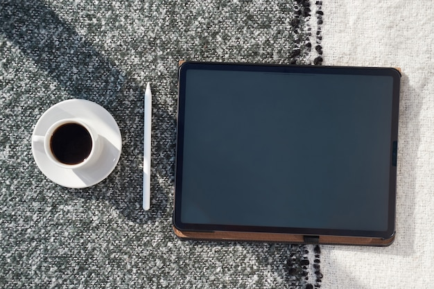 タブレットと黒と白の格子縞のコーヒーカップのセット。