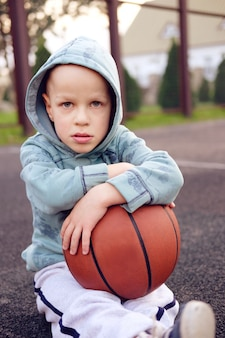Малыш сидит с баскетбольным мячом на баскетбольной улице