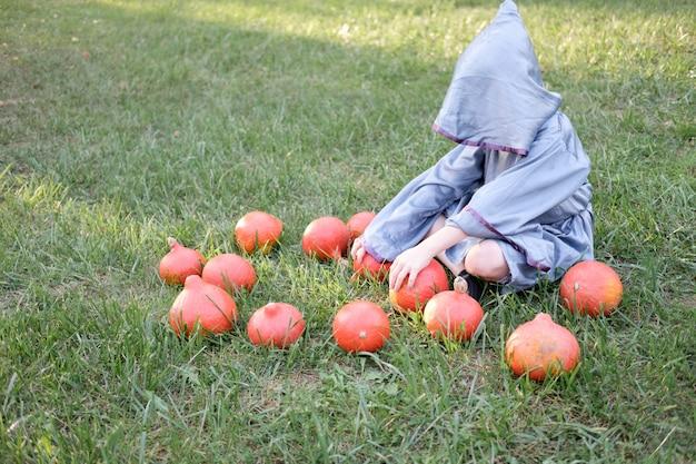 ウィザードの衣装を着た少年は芝生の上に座って、カボチャを保持しています。ハロウィーンのコンセプト。