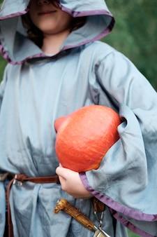 カボチャを保持しているウィザードの衣装の少年をクローズアップ。ハロウィーンのコンセプト。