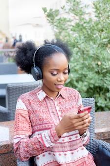 Черная афро девушка в этнических платье с наушниками на шее, сидя в открытом воздухе кафе, набрав в смартфон и улыбается.